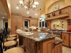 Mediterranean Kitchen With Two-Tiered Granite Island and Bar Seating
