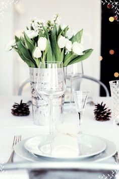Simply beautiful. White tulips, white china, crystal, silver, pine cones.