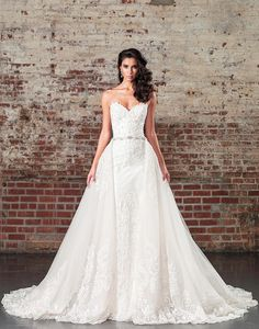 Walk down the aisle in this strapless sweetheart gown with a detachable cathedral length skirt with buttons to the end of the train. The straight silhouette of this gown is perfect to dance the night away in after the ceremony featuring an attached beaded belt and allover lace appliques. Available without the train as style 9862D.