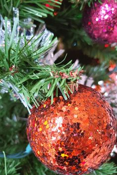 2021 cozy Christmas aesthetic for hygge Christmas. Yule ideas for pagans. A faux Christmas tree with glitter bulbs in orange and magenta. Cozy Christmas aesthetic.