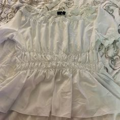 White off shoulder peasant top White silky peasant top. Elastic around the waist and shoulders. The top goes off the shoulders. Perfect date night or night on the town top. Tops