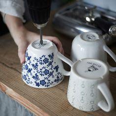 Jemand bohrt mit einem Akkubohrer Löcher in drei Teetassen.