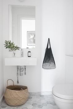 All white bathroom and straw bucket for towels