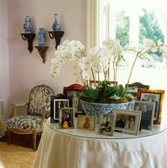 Beautiful and interesting combination of the white orchids in the blue white bowl and the picture frames on the skirted table.