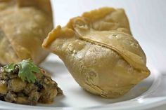 Samosa - A popular snack made out of flour filled with spicy boiled potatoes - Indian Food N, Food And Drink, Delicious Recipes, Yummy Food, Samosa Recipe, Samosas, International Food, Food Goals, Spring Rolls