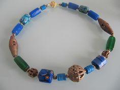 MIRACLE  Frisches Collier, jede einzelne Perle von Hand angefertigt, komponiert aus: einer mittig platzierten antiken, raren Afrika Handelsperle aus Messing, je zwei antiken Handelsperlen aus Ghana in mittel- und himmelblau, zwei seltene grüne Handelsperlen aus Ghana, vier raren antiken Walzen in Kobaltblau, zwei antiken Bronze Bicone-Perlen, himmelblauen Vulcanit- Handelsperlen aus Afrika   und kleinen goldenen Messingperlen. Schließe ist ein diamantierter, vergoldeter Magnetverschluß.