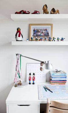 Mads-Emilin huoneessa on paljon pikkutavaroita ja jalkapallo-harrastuksesta kertovia esineitä. Koulupöytä on Ikeasta. Stokken tuoli on ollut käytössä vauvasta saakka.