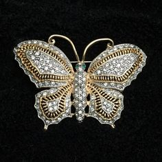 Vintage Gold & Silver Rinestone Butterfly Brooch Beautiful vintage butterfly brooch pin. Gold and silver tones. Loaded with clear rhinestones and two green rhinestone eyes. It does have one clear stone missing on the top of the left wing. 1.75 inches long. 2.5 inches wide. Unsigned. Good vintage condition. Jewelry Brooches