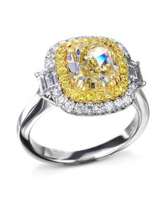 Platinum and 18 karat yellow gold ring set with a carat fancy yellow cushion-cut diamond center surrounded by 22 fancy yellow round diamonds CTW), 26 round brilliant cut diamonds CTW), and 2 trapezoid diamond side stones CTW). Yellow Diamond Rings, Halo Diamond, Diamond Cuts, Cushion Cut Diamonds, Round Diamonds, Unique Diamond Engagement Rings, Brilliant Diamond, Ring Designs, White Gold