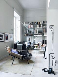 HEM&RUM.se | White living room with a Flag Halyard chair, a black leather sofa, cushion from Svenskt Tenn and a bookshelf.
