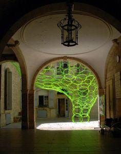 Green hula hoops in stone courtyard.