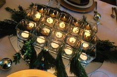 "Christmas ornaments, wrapping paper, and votive candles!  Wrap a couple of boxes with festive paper, and incorporated ball ornaments into glass vases, napkin rings, and a hanging ""chandelier.""  Grouping votive candles together in the center of the table gives a bigger impact than lining them down the table individually.  A little bit of greenery cut fresh from your tree and you have a beautiful holiday tablescape."