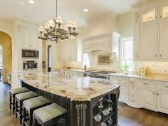 Culinary Inspiration: Kitchens with Class | The beautiful white custom cabinetry contrasts beautifully with the black and marble kitchen island. At 7603 Bryn Mawr Drive in Highland Park.