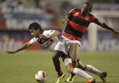 Diego Gonzalez (L) of Argentina's Lanus is tackled by Willians of Brazil's Flamengo during their Copa Libertadores soccer match at the Joao Havelange stadium in Rio de Janeiro April 12, 2012.