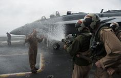 """Sailors assigned to the """"Gauntlets"""" of Electronic Attack Squadron (VAQ) 136, spray Cmdr. Christopher Hunter, commanding officer of VAQ 136, with a fire hose following his last flight as a Naval aviator on the flight deck of aircraft carrier USS Carl Vinson (CVN 70)."""