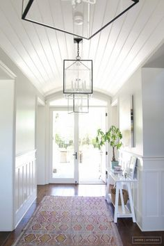 All white entry way with hanging clear lamp, white working bench, potted plant, colorful rug
