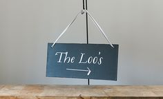 """Rectangular chalkboard sign for hanging, reading """"The Loos"""" in a scrolling font, with an arrow to the right. A decorative sign, offering a lighthearted way to direct guests to the toilets. Perfect for both indoor and outdoor ceremonies. Bespoke colour, word and font options are also available. For more informationdrop us a line. Dimensions Length: [&hellip"""