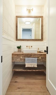Farmhouse Farmhouse-style bathroom features half wall shiplap wainscoting with wallpaper above, wide plank hardwood flooring, reclaimed wood mirror, wall-mounted faucet, vessel sink and reclaimed wood freestanding vanity with shelf for baskets by donna Bad Inspiration, Bathroom Inspiration, Guest Bathrooms, Small Bathroom, Bathroom Ideas, Bathroom Designs, Bathroom Remodeling, Half Bathrooms, Bathroom Organization