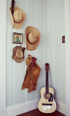 This gallery wall is a collection of hats and other cowboy-themed collectibles.