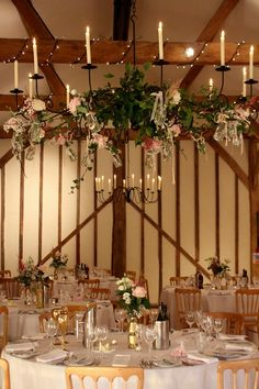 Candelabras in the South Barn at Upwaltham Barns decorated with ivy and hanging jars filled with flowers.