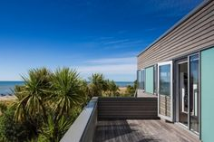 An outdoor room faces east with views through trees to the sea