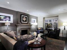 Este salón cuenta con una pared de acento gris oscuro situado detrás de una chimenea pintada de color gris claro. Un sofá neutral con almohadas florales se posiciona frente a los sillones de cuero negro, mientras que una mesa de café de cristal se encuentra en el centro de la habitación. menos ...
