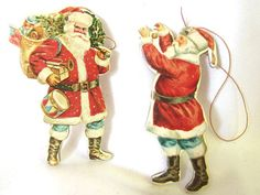 Vintage 1977 Christmas ornaments from Merrimack feature die cut cardboard Santas. Great, old fashioned Santas dressed in red a blue, one carries an evergreen tree and a sack of toys on his back. The other looks like hes taking a selfie, but hes hanging an ornament. Both have gold hanging loops.  They are 3 inches (7.6 cm) tall.  Condition: Excellent  Check here for more miscellaneous ornaments: http://www.etsy.com/shop/bythewaysidexmas?section_id=15787854  Thanks for looking! I am happy to…