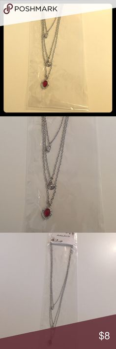 """Silver layered necklace with red accent One clasp holds these three adorable necklace strands together for a layered look! Silver chain. One necklace has a faux diamond stone, one has a silver circular charm, and one has a silver and red charm. 11"""" long. Price is firm. Jewelry Necklaces"""