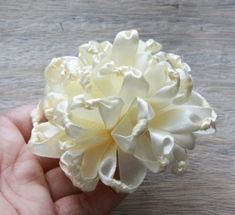 Small lengths of satin ribbon are knotted in middle of each piece of ribbon, then knotted lengths are gathered together to form flower. I by stella_fresa