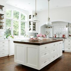In this causal but sophisticated white kitchen, walnut accents and subtle texture and softness add warmth and depth. Shades of white dominate on clean-lined Shaker-style cabinetry, on the tile surrounding the range, and on gray-veined marble on the sink-wall backsplash.