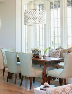 this dining room is shabby chic because of the plush chairs and pillows with different colors and patterns.