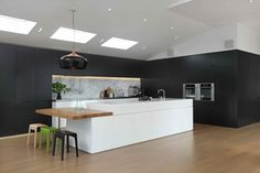 Masons Ave Kitchen. Contemporary kitchen design. Black and white kitchen. Floor to ceiling cabinetry. Block island with cantilevered wood bench top. Scandinavian. Marble splash back. Cabinetry with integrated handles are a chic design detail to any kitchen. By Sonya Cotter Design