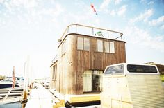 A New York City houseboat with wooden exterior and a rooftop lounge area