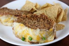 """Taco Meatloaf {the Blog Chef}..""""This meatloaf combines ground beef, corn chips, salsa, Mexican cheese and various seasoning. The meatloaf is topped in the oven with a mixture of refried beans and salsa."""""""