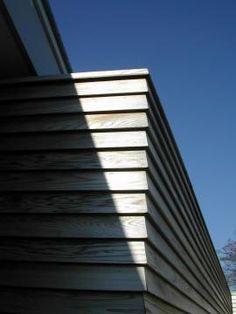voor de bekleding van een kantooruitbouw zijn de smalle red ceder delen zodanig gevormd dat een geschubd oppervlak ontstaat. dakrand afwerking en raamdorpel zijn in hetzelfde materiaal uitgevoerd