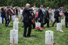 U.S. President Donald Trump (C) points while walking through Section 60 at Arlington National Cemetery on Memorial Day May 29, 2017 in Arlington, Virginia. Trump visited with families and layed flowers at the grave of Marine Corps Second Lt. Robert Kelly, the son of Homeland Security Secretary John Kelly.