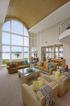 Soaring, two story living room with immense full height arched glass facade and vaulted natural wood ceiling. White railing catwalk overlooks a set of contemporary light brown seating with glass topped natural wood coffee table.
