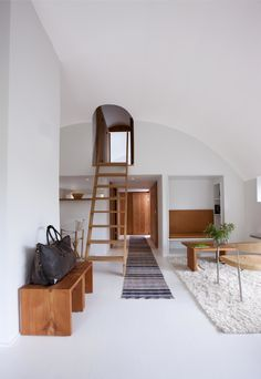 The architects installed plaster walls and a curved ceiling that lets in more light. Its circular design repeats in the entrance to the master bedroom, accessible by a ladder.