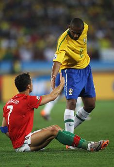 Maicon of Brazil helps up Cristiano Ronaldo of Portugal during the 2010  FIFA World Cup South Africa Group G match between Portugal and Brazil at  Durban ... fe2b527c0