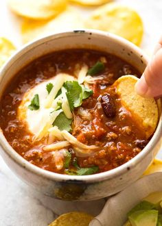 Chili Con Carne: Corn chip being dipped into a bowl of Chili topped with sour cream, grated cheese and cilantro Chilli Recipes, Mexican Food Recipes, Beef Recipes, Soup Recipes, Dinner Recipes, Cooking Recipes, Healthy Recipes, Slow Cooking, Chilli Con Carne Recipe