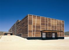 Olisur olive oil factory by GH + A Architects  The building comprises the company offices and factory, and is made of concrete clad in wood and glass.
