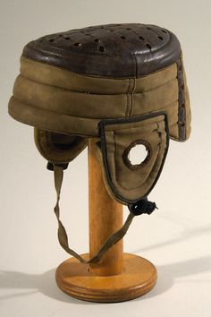 """Canvas and leather flat top football helmet c.1900-10. Early canvas helmet retains its original canvas chin strap (partially detached) with the leather trim and top including air holes. The cotton lining is fully intact and the leather top is still soft and supple with a 3"""" dry area on one side of the leather top rim with a bit a chaffing. $750"""