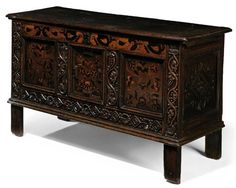 A CHARLES I OAK AND MARQUETRY CHEST  EARLY 17TH CENTURY, YORKSHIRE.  The frieze with scrolling leaf-work above three panels with stylised flowers and flanked by trailing berried vine uprights, with lozenge and rosette lower rail and lozenge-carved sides