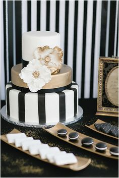 Black and white wedding cake with gold accents.