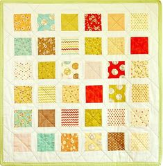 Whimsical Charm Pack Baby Quilt - This free pattern for a baby quilt mixes tones of chartreuse, crimson, and aqua for bright and cheery baby quilts. White sashing between colorful charm squares makes the Whimsical Charm Pack Baby Quilt especially bold.