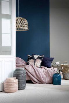 slaapkamer met donkerblauwe muur en roze sprei