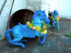 """rescued these Wonder Horses from the trash, nice horses, bad paint jobs, so repainted with Rustoleum 2x in Seaside, Lagoon, and a purple for a """"seahorse"""" effect. Added silk garland (on sale) as leis. Brightens up a back walk that was boring. NEVER REPAINT ACTUAL COLLECTORS ITEMS LIKE BREYER MODLES!!!"""