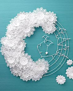 a string of twinkle lights and doilies on a wire wreath-form= snowflake wreath  Probably should use the LED lights, they don't get as hot as the old lights.