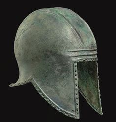 A GREEK BRONZE HELMET OF ILLYRIAN TYPE   ARCHAIC PERIOD, CIRCA 6TH CENTURY B.C.   Of hammered sheet, with a wide flaring neck-guard, two sets of three raised parallel ridges running front to back across the crown, a perforation between each end, likely for attachment of a crest, a raised ridge around the perimeter with evenly-spaced bronze rivets along the edge, each cheek-guard perforated at the forward tip within the border, with two horizontal ridges across the brow  8 7/8 in. (22.5 cm.)…