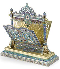 A Russian Gilded Silver and Cloisonné Enamel Letter Holder, Antip Kuzmichev, Moscow; Retailed by Tiffany & Co., 1887, the panels elaborately pierced and enameled with floral and geometric ornament, raised on shaped, enameled columns, set on a tapering rectangular base enameled with scrolls, anthemia, flowerheads, and bands of hearts stamped made for Tiffany & Co. on base and with dedicatory inscription dated Christmas 1887 on underside. Height 7 in. 17.8 cm